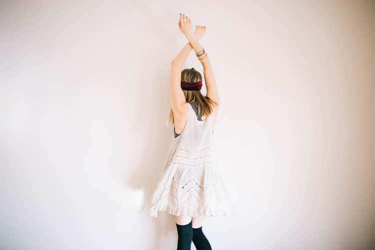 Kvinne med bind for øynene og armene over hodet