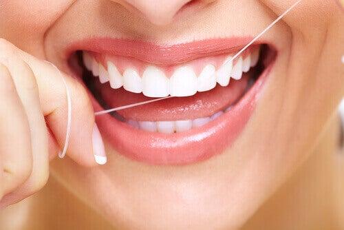 Kvinne bruker tanntråd