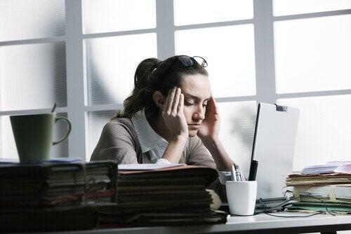 Kvinne med stresshodepine foran en datamaskin på jobben