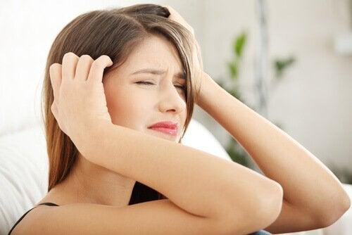 Ung kvinne med stresshodepine i smerte
