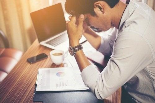 Ung mann med hodepine ved skrivebordet sitt på et kontor
