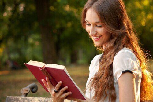 Lykkelig kvinne leser bok alene