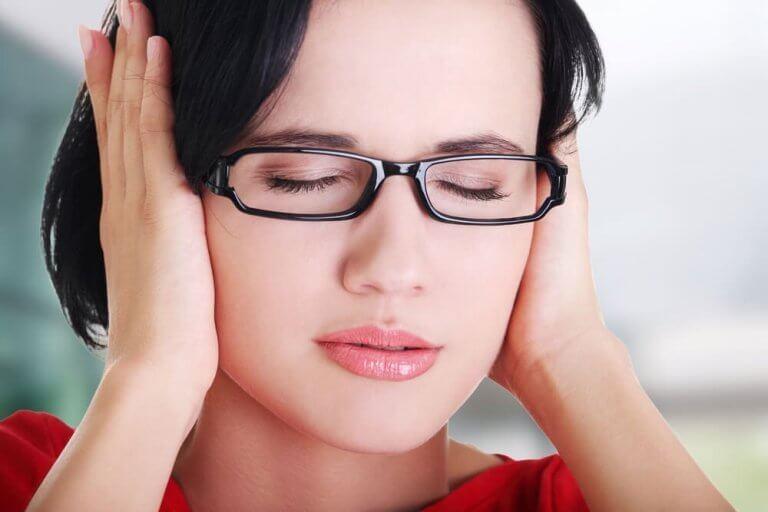 Kvinne med lukkede øyne holder for ørene