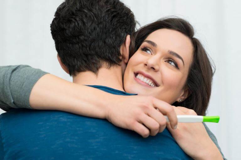 Gravid kvinne gir klem til mann