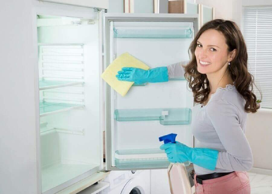 Kvinne rengjør kjøleskapet