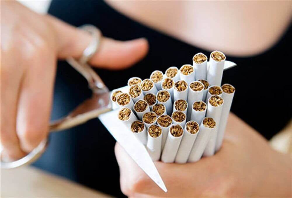 Kvinne klipper sigaretter med saks