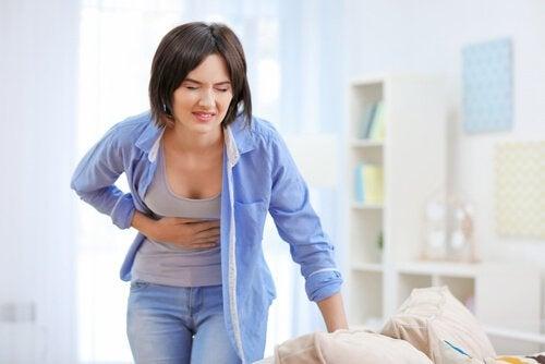 Kvinne i blå skjorte med leversmerter og magesmerter