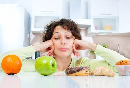 Kvinne ser på sunne og usunne matvarer