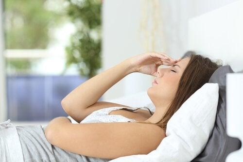 Kvinne som ligger i sengen med hodepine