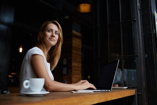 Kvinne med PC og kaffe