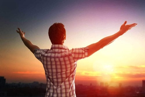 Glad mann ser på solnedgang