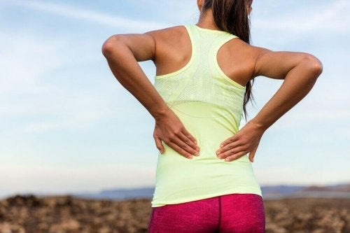 Kvinne med treningsklær har ryggsmerter