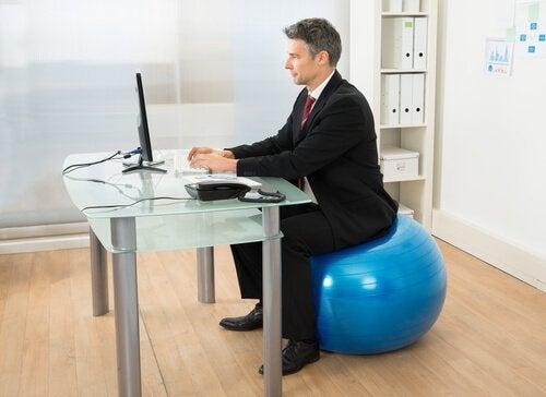 Mann sitter på treningsball og jobber
