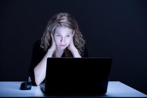 Trist kvinne ser på PC-skjerm
