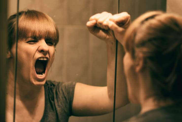 Kvinne kjefter på seg selv i speilet