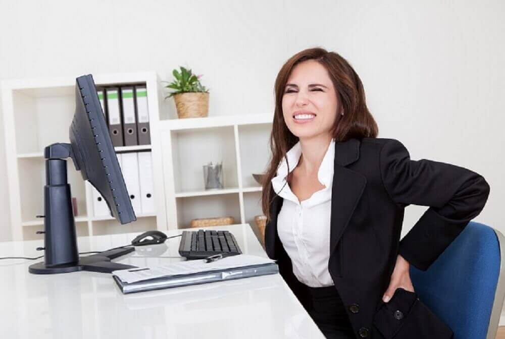 Kvinne på kontoret med ryggsmerter