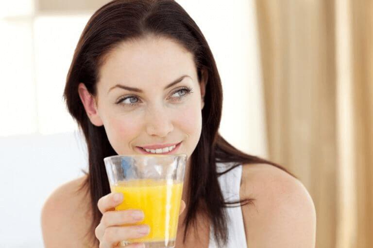 Kvinne drikker ananasjuice