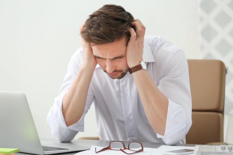 Mann med hodepine på jobb