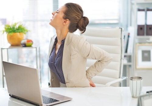 Kvinne med på jobb med smerter i ryggen