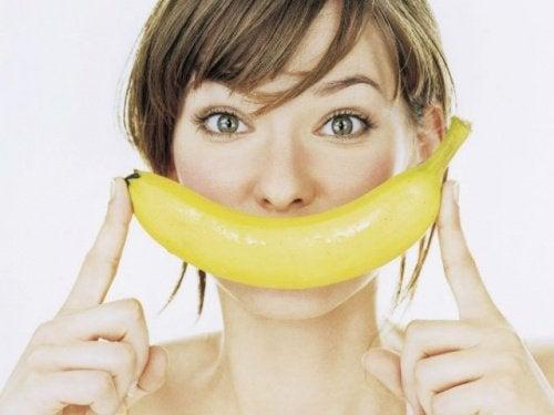 Kvinne holder en banan foran munnen som et smil