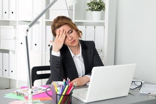 En kvinne som er trøtt på kontoret sitt.