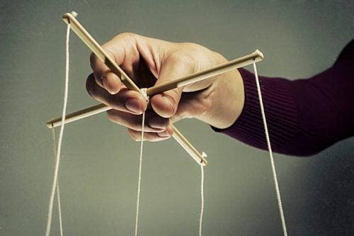 Hånd kontrollerer marionett