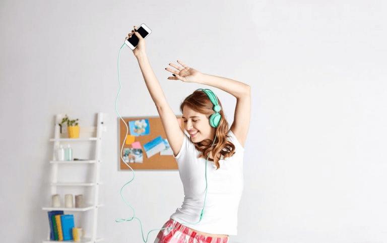 Jente danser og lytter til musikk