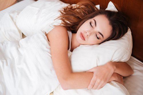 Kvinne sover og holder rundt puten sin
