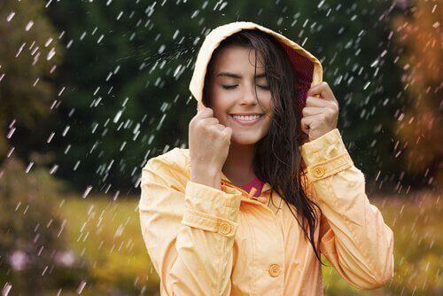 Glad kvinne i regnet