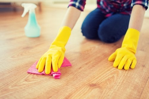 Kvinne prøver å holde huset rent ved å rengjøre gulvet
