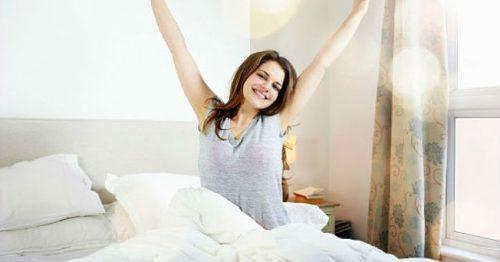 Glad kvinne står opp om morgenen