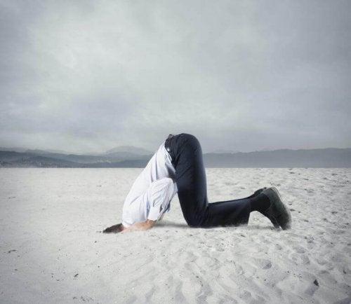 Mann med hodet i sanden