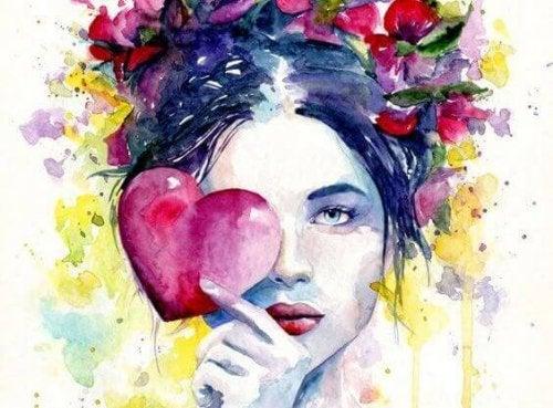 Kvinne holder et hjerte foran øyet