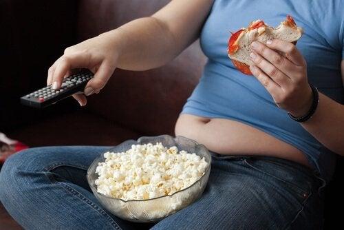 Kvinne spiser popcorn og kommer til å gå opp i vekt