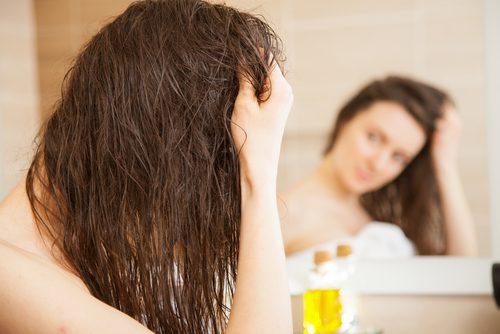 Kvinne bruker olivenolje i håret