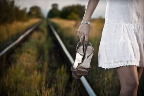 Kvinne går med sko i hendene