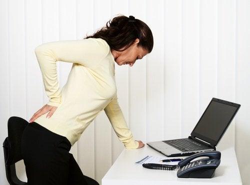 Kvinne med smerter i korsryggen