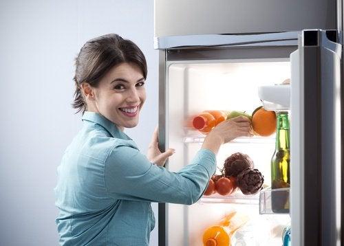 Kvinne oppbevarer mat i kjøleskap