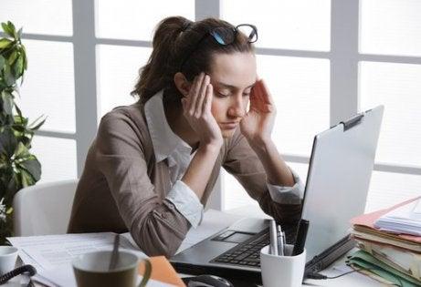 Kvinne med hodepine på jobb