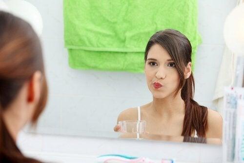 Kvinne bruker naturlige munnskyllevann