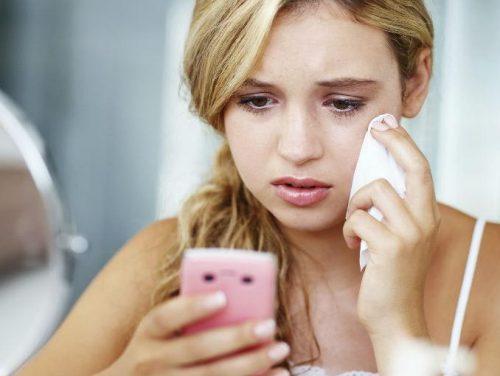Kvinne gråter ved telefon