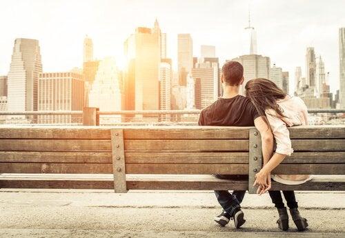 Lykkelig par sitter på en benk
