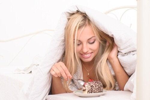 Kvinne spiser kake i sengen