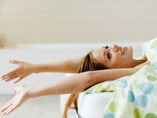 Kvinne tøyer ut i sengen