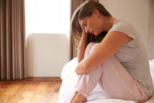 Deprimert kvinne i sengen