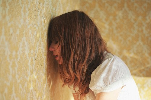 Kvinne lener hodet mot en vegg