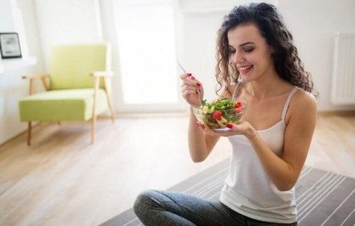 Kvinne spiser sunn salat