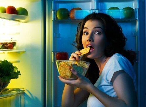 Kvinne spiser usunn snacks