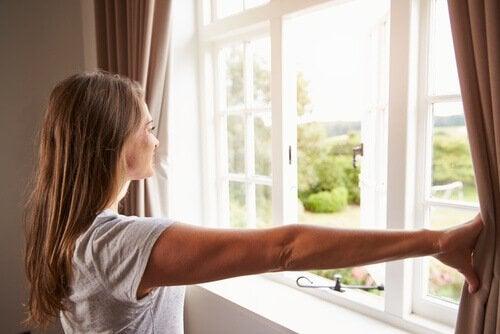 Kvinne åpner gardiner
