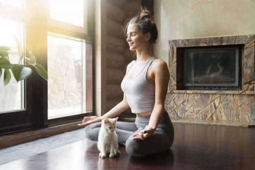 Kvinne mediterer med katt